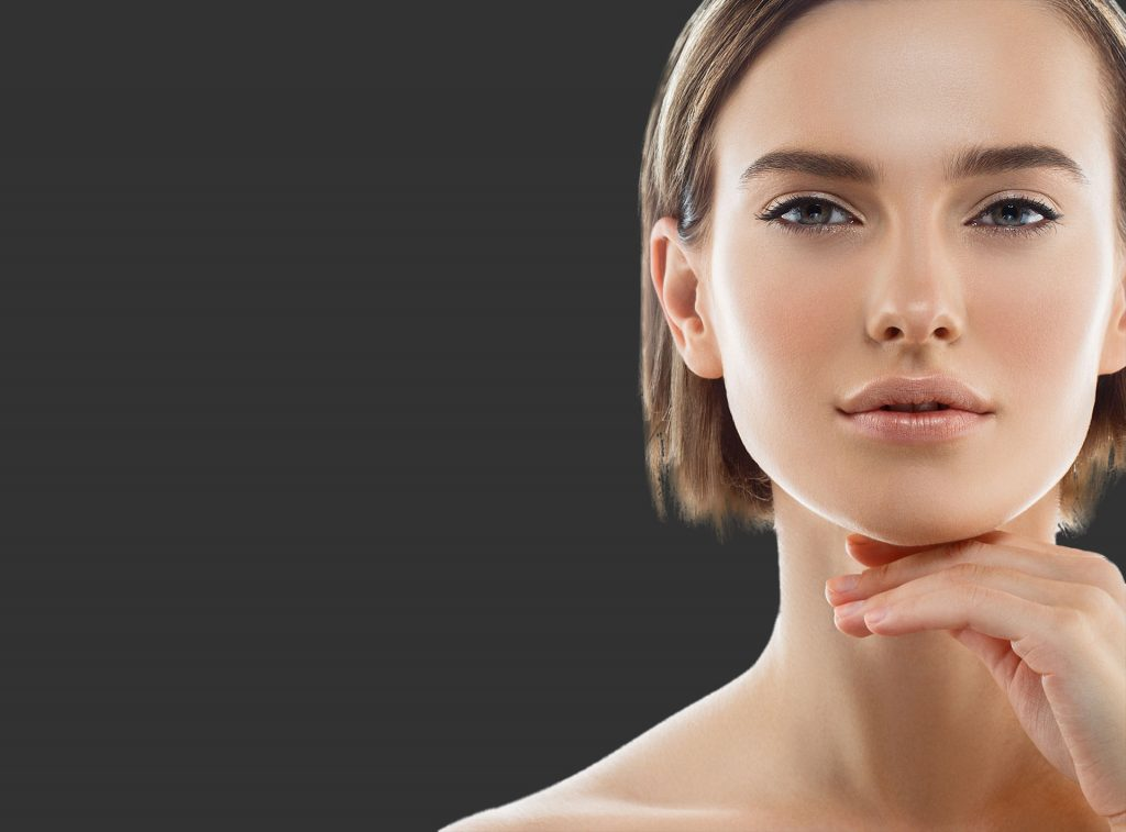 woman with makeup and hand on chin